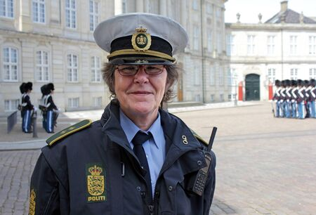 COPENHAGEN - MAY 15, 2012: Unknown Danish policewoman during the ceremony of changing the Royal Guards at Amalienborg Palace on May 15, 2012. This palace is the Danish Royal residence and a top tourist attraction as well. Stock Photo - 16704771