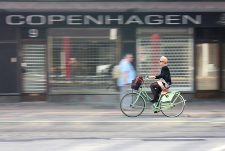 COPENHAGEN - MAY 20, 2012: Female cyclist riding quickly along Ved Vesterport street in Copenhagen on May 20, 2012. Intentional in camera motion blur.
