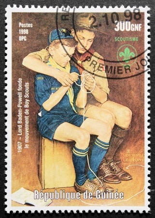 GUINEA - CIRCA 1998. A postage stamp printed by GUINEA shows two Boy Scouts, circa 1998. Editorial