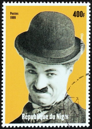 chaplin: NIGER - CIRCA 1999: A postage stamp printed by NIGER shows image portrait of famous English comic actor and filmmaker Sir Charles Spencer Charlie Chaplin, circa 1999.