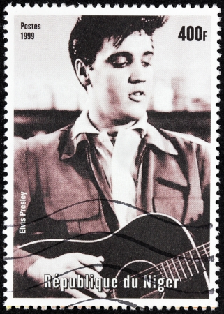 elvis: NIGER - CIRCA 1999: A postage stamp printed by NIGER shows image portrait of famous American singer Elvis Presley, circa 1999.