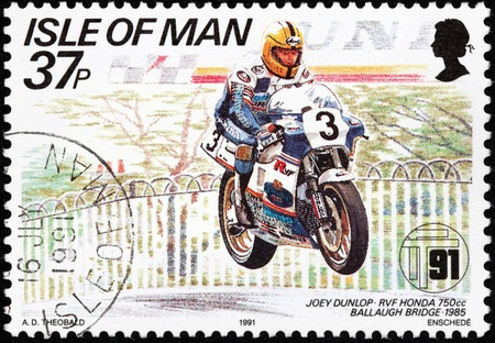ISLE OF MAN - CIRCA 1991: a stamp printed by GREAT BRITAIN shows winner of International Isle of Man TT (Tourist Trophy) Race - the most prestigious motorcycle race in the world, circa 1991. Stock Photo - 21487387