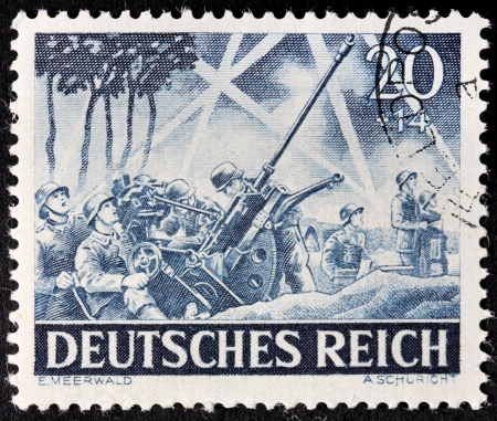 firepower: GERMANY - circa 1943: stamp printed by Germany, shows German anti-aircraft gun in action against bombers, circa 1943.