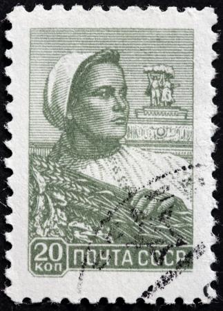 USSR - CIRCA 1958: Een stempel gedrukt door de USSR (Rusland) toont een vrouw boerderij arbeider die een tarwe bundel, circa 1958.