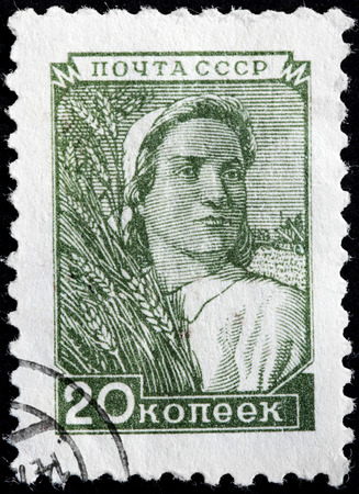 USSR - CIRCA 1948: A stamp printed by USSR (Russia) shows a woman farm worker holding a wheat bundle, circa 1948.