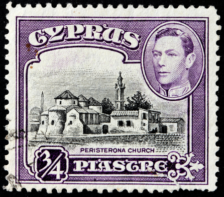 st hilarion: CYPRUS - 1938: A stamp printed by CYPRUS shows image portrait of King George VI and view of the Church of St. Barnabas and St. Hilarion, Peristerona, 1938 Editorial