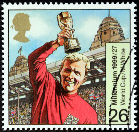 english famous: UNITED KINGDOM - CIRCA 1999: A stamp printed by United Kingdom shows image portrait of famous English footballer Bobby Moore with the World Cup, circa 1999.