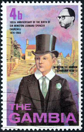 harrow: GAMBIA - CIRCA 1974: A stamp printed by GAMBIA shows image portrait of young Winston Churchill the Harrow schoolboy aged 12 against view of Harrow School, circa 1974