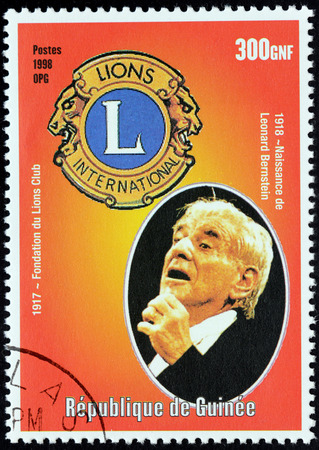 leonard: GUINEA - CIRCA 1998: a postage stamp printed by Guinea shows image portrait of famous American composer, conductor, author, music lecturer, and pianist Leonard Bernstein, circa 1998.