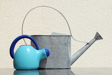 Two watering cans against wall at the sunny summer day. Selective focus limited to front watering cans. photo