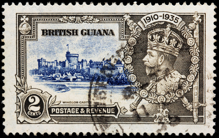 BRITISH GUIANA - CIRCA 1935: A stamp printed by BRITISH GUIANA shows view of Windsor Castle and image portrait of Georg V - King of the United Kingdom and the British Dominions, circa 1935 Editorial
