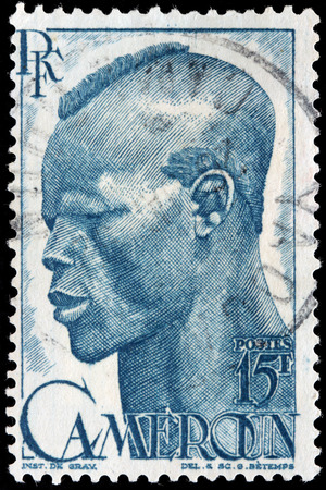 cameroonian: CAMEROON - CIRCA 1946: A stamp printed by FRANCE shows image portrait of young native man, circa 1946.