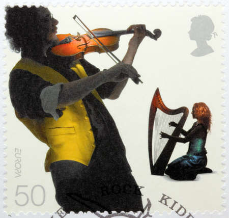fiddler: UNITED KINGDOM - CIRCA 2006: A stamp printed by GREAT BRITAIN shows two European musicians - fiddler and harpist, circa 2006
