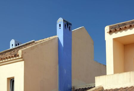 gables: Abstract view of gables of Mediterranean houses painted in traditional colors against deep blue sky.