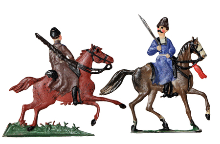 cossacks: Set of two ancient tin toy soldiers. Russian armed by saber and rifle cossacks horsemen in traditional clothes against white background. Stock Photo