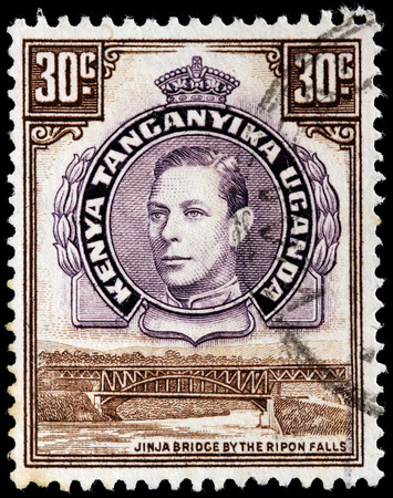 vi: KENYA, TANGANYIKA, UGANDA - CIRCA 1952: A stamp printed by EAST AFRICAN COMMUNITY shows image portrait of King George VI against view of the Jinja bridge by the Ripon falls, circa 1952 Editorial