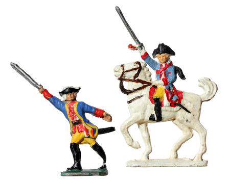 dashing: Set of two ancient tin toy soldiers. Prussian armed by swords infantry soldier and officer horseman against white background. Prussian infantry 1760.