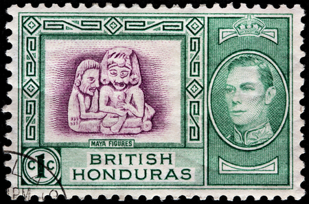 vi: BRITISH HONDURAS - CIRCA 1938: A stamp printed by BRITISH HONDURAS shows image portrait of King George VI and ancient Maya figures from Stann Creek, circa 1938 Editorial