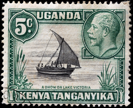 v lake: EAST AFRICAN COMMUNITY - CIRCA MAY, 1935: A stamp printed by EAST AFRICAN COMMUNITY shows portrait of King George V against traditional sailing vessel Dhow on Lake Victoria Editorial