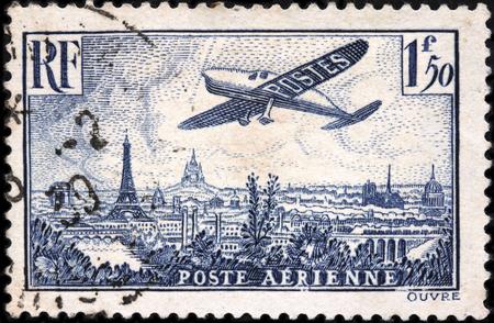 poststempel: FRANKREICH - Februar 1936: Ein Stempel von Frankreich gedruckt zeigt Flugzeug über Paris fliegen. Schöne Paris Stadtbild mit Eiffelturm, die Kathedrale Notre Dame und Sacre Coeur auf dem Montmartre Hügel Editorial