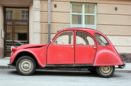 classical mechanics: Side view of old small red car at European street.
