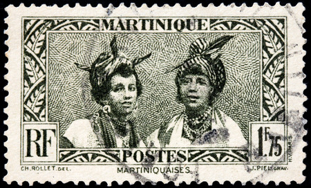 post stamp: MARTINIQUE - AUGUST 10, 2015: A stamp printed by MARTINIQUE shows image portraits of two young Martinique women, circa May, 1933.
