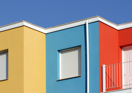 mediterranean houses: Abstract view of facades of Mediterranean houses painted in traditional colors against deep blue sky