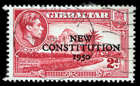 vi: LUGA, RUSSIA - JUNE 25, 2016: A stamp printed by GIBRALTAR shows image portrait of King George VI against view of Gibraltar Rock North Side, circa 1943 (New Constitution Overprint at 1950) Editorial