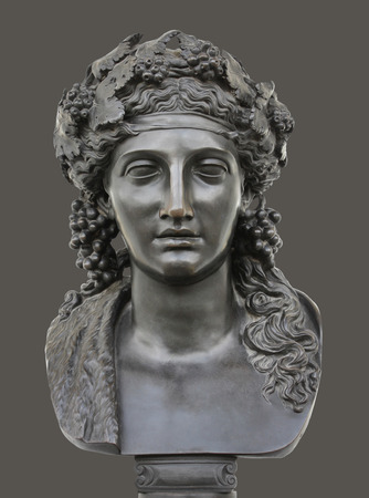 Ancient bronze statue of Dionysus isolated on a dark grey background. Dionysus is the Olympian God of the grape harvest, wine and merriment. He was also known as Bacchus.