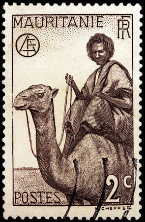 camel post: LUGA, RUSSIA - NOVEMBER 29, 2016: A stamp printed by MAURITANIA shows Nomand Man on Dromedary against native desert landscape, circa 1938 Editorial