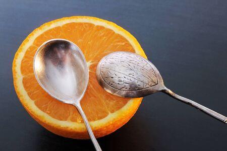 Closeup view of half juicy orange and two beautiful vintage spoons against dark blue background.