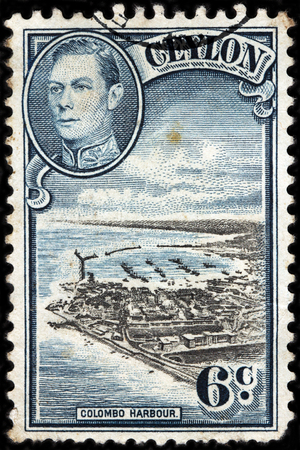 royal: LUGA, RUSSIA - FEBRUARY 7, 2017: A stamp printed by CEYLON shows image portrait of King George VI against beautuful view of Colombo harbor. Colombo is largest city of Sri Lanka, circa 1938.
