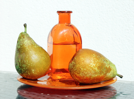 old desk: Two juicy ripe golden pears and vintage glass bottle with cider. Stock Photo