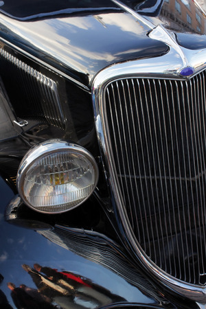 A closeup of beautiful details of vintage black car on the front side. Shallow depth, selective focus. Suitable for an abstract background. Stock Photo