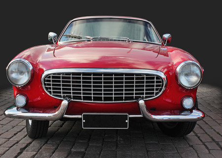 Beautiful vintage red car front view against dark background