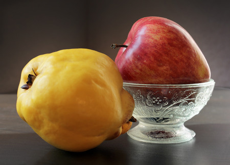 Closeup view of ripe yellow quince and juicy red apple in vintage glass vase against a low key background. Choose a focal point. 版權商用圖片 - 100253601