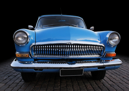 Beautiful vintage blue car front view against dark background