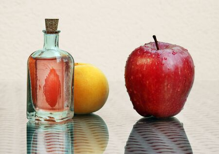 Still life with fresh compote in vintage glass bottle, red ripe apple and juicy peach against a high key background with amazing reflections. Selective and soft focus. Banque d'images