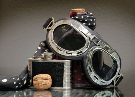 Still life with aviation style goggles, black vintage hip flask, polka dot headscarf and walnut against a low key background. Shallow depth, selective focus.