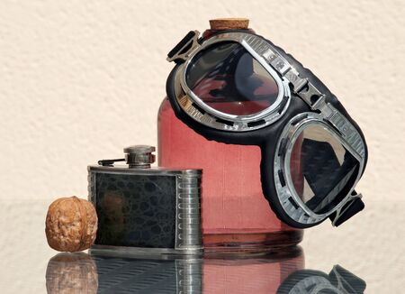 Still life with aviation style goggles, black vintage hip flask and walnut with amazing reflections against high key background. Space for your text. Shallow depth, selective focus.