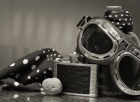 Aviation style goggles, black vintage hip flask, polka dot headscarf and walnut against a low key background. Still life in sepia tone with space for your text. Shallow depth, selective focus.