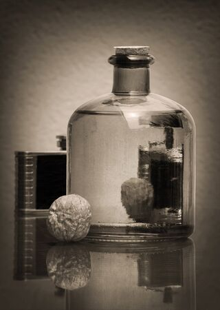 Still life in sepia tone with transparent glass bottle, black vintage hip flask, and walnuts against a low key background with amazing reflections. Shallow depth, selective focus.