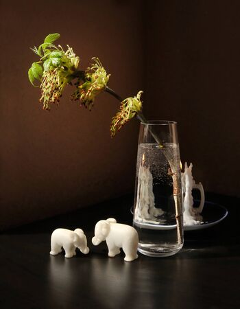 Still life with flowering spring twig of ash-tree with young leaves in a glass vase, two small toy elephants and burning candle against a low key background. Selective and soft focus.