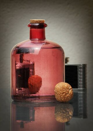 Still life with transparent glass bottle, black vintage hip flask, and walnuts against a low key background with amazing reflections. Shallow depth, selective focus.