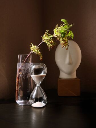 Still life with flowering spring twig of ash-tree with young leaves in a glass vase and vintage sandglass against a low key background. Selective and soft focus.  Standard-Bild