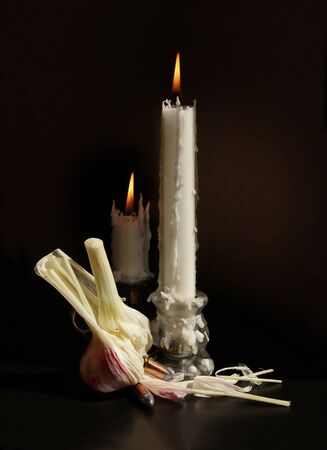 Still life with two candlesticks with burning candles, garlic bulb and two handgun cartridges with silver bullets against a low key background. Shallow depth, selective focus.