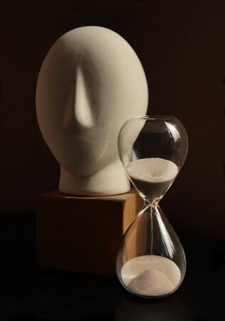Art studio still life with plaster sculpture of man head and vintage sandglass against low key background. Selective and soft focus.