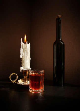 Still life with black bottle, fruit liqueur in the small glass, and vintage candlestick with burning candle against a low key background. Selective and soft focus. 写真素材