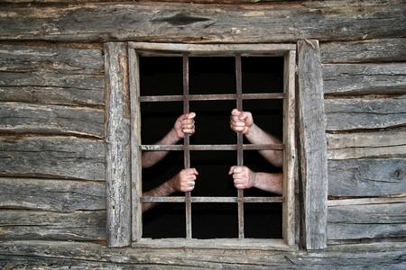 break out of prison: Men hands behind prison bars in old cottage