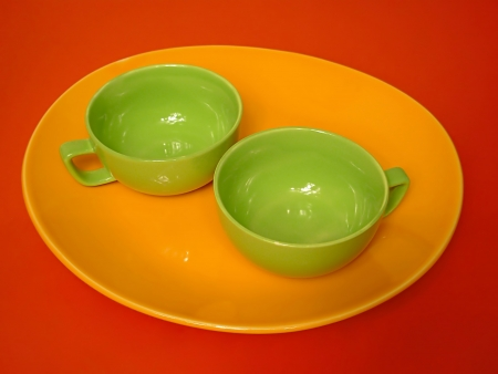 Mini tea set on the red background,isolated objects